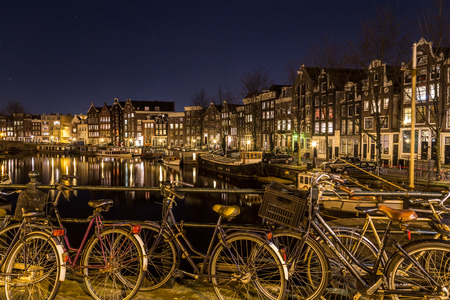 dutch canal house: AMSTERDAM, NETHERLANDS - 16TH FEBRUARY 2016: A view along the Waalseilandgracht Canal in Amsterdam at night with bikes in the foreground.