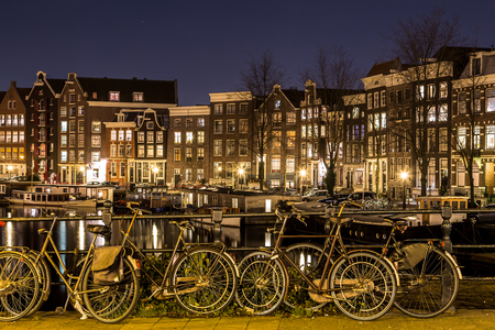 decorated bike: A view along the Waalseilandgracht Canal in Amsterdam at night with bikes as the main focus in the foreground.