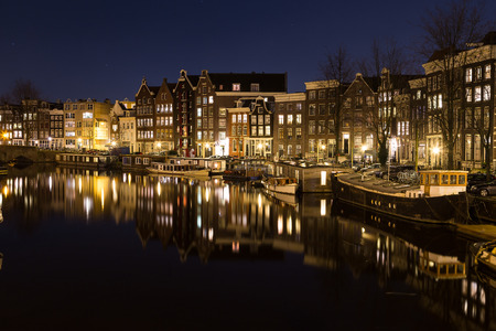 dutch canal house: A view along the Waalseilandgracht Canal in Amsterdam at night. Building, boats and reflections can be seen. There is space for text.