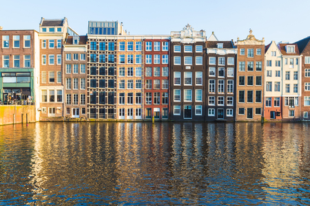 dutch canal house: Old Buildings along the Damrak in Amsterdam during the day. Reflections can be seen in the water.
