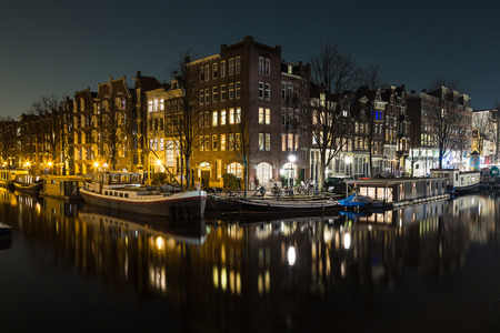 dutch canal house: A view of buildings and boats along the Amsterdam Canals at night. Reflections can be seen in the water. There is space for copy space.