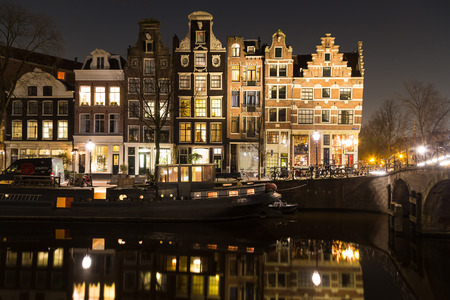 dutch canal house: AMSTERDAM, NETHERLANDS - 17TH FEBRUARY 2016: A view of buildings and boats along the Amsterdam Canals at night. Reflections can be seen in the water. There is space for copy space.