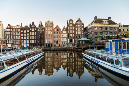dutch canal house: AMSTERDAM, NETHERLANDS - 16TH FEBRUARY 2016: Old Buildings along the Damrak in Amsterdam during the day. Boats can be seen.