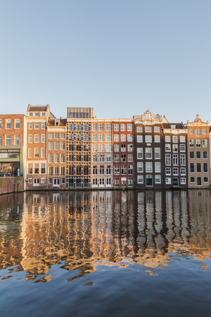 dutch canal house: AMSTERDAM, NETHERLANDS - 16TH FEBRUARY 2016: Old Buildings along the Damrak in Amsterdam during the day. Editorial