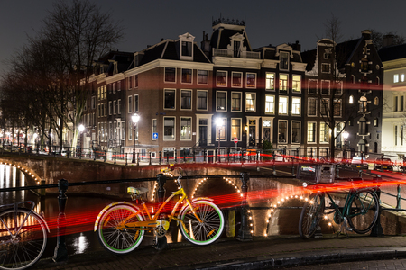 dutch canal house: AMSTERDAM, NETHERLANDS - 17TH FEBRUARY 2016: A view of bridges, buildings and bikes at the Leidsegracht and Keizersgracht canal intersection in Amsterdam at night. The trail from traffic can be seen.