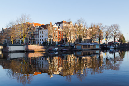 dutch canal house: AMSTERDAM, NETHERLANDS - 16TH FEBRUARY 2016: A view along Oudeschans Canal in Amsterdam in the morning. Buildings, boats, cars, bikes and people can be seen.