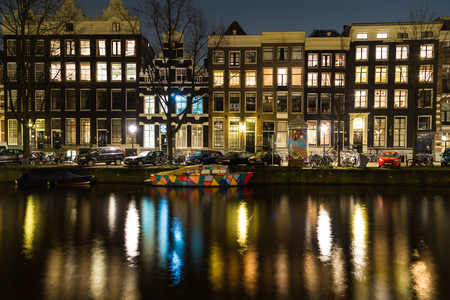 dutch canal house: AMSTERDAM, NETHERLANDS - 17TH FEBRUARY 2016: Amsterdam buildings and a colorful boat in the canal at night. Reflections can be seen.