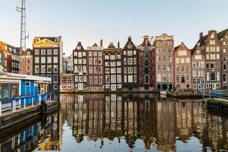 dutch canal house: AMSTERDAM, NETHERLANDS - 16TH FEBRUARY 2016: Old Buildings along the Damrak in Amsterdam during the day. Part of the docks can be seen.