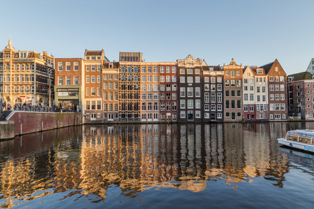 dutch canal house: AMSTERDAM, NETHERLANDS - 16TH FEBRUARY 2016: Old Buildings along the Damrak in Amsterdam during the day. People can be seen.