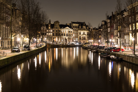 dutch canal house: AMSTERDAM, NETHERLANDS - 17TH FEBRUARY 2016: A view of buildings and boats along the Amsterdam Canals at night.