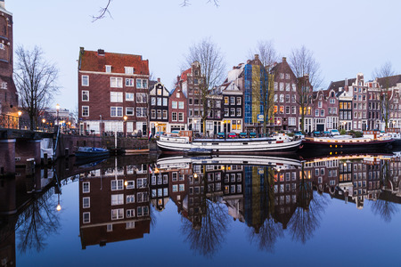 dutch canal house: AMSTERDAM, NETHERLANDS - 16TH FEBRUARY 2016: A view along the Waalseilandgracht Canal in Amsterdam at twilight. Building, boats and reflections can be seen.