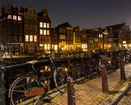 dutch canal house: Bikes chained to railings along the Canals in Amsterdam. Buildings can be seen in the background. There is space for text.