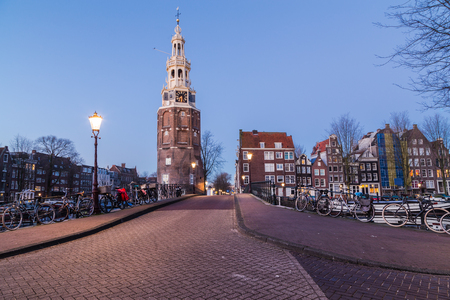 dutch canal house: A view along Oudeschans Street towards the Montelbaanstoren Tower in Amsterdam at twilight. Building, boats and bikes can be seen.