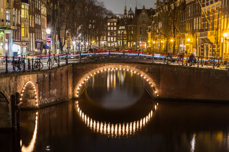 dutch canal house: A view of the bridges at the Leidsegracht and Keizersgracht canals intersection in Amsterdam at dusk. Bikes and buildings can be seen. The trail of traffic can be seen on a bridge.