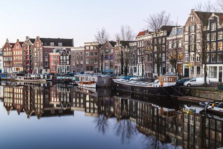 dutch canal house: A view along the Waalseilandgracht Canal in Amsterdam in the morning. Building, boats and reflections can be seen. There is space for text.