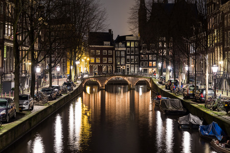 dutch canal house: AMSTERDAM, NETHERLANDS - 17TH FEBRUARY 2016: A view along the  Leidsegracht canal in Amsterdam at night. Buildings, boats and buildings can be seen.
