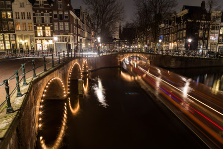 dutch canal house: A view of the bridges at the Leidsegracht and Keizersgracht canals intersection in Amsterdam at dusk. Bikes and buildings can be seen. The trail from a boat can be seen.