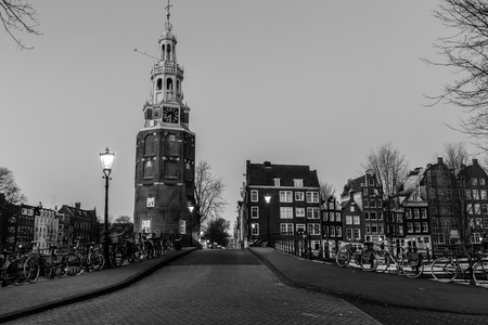 dutch canal house: AMSTERDAM, NETHERLANDS - 16TH FEBRUARY 2016: A view along Oudeschans Street towards the Montelbaanstoren Tower in Amsterdam at twilight. Building, boats and bikes can be seen.