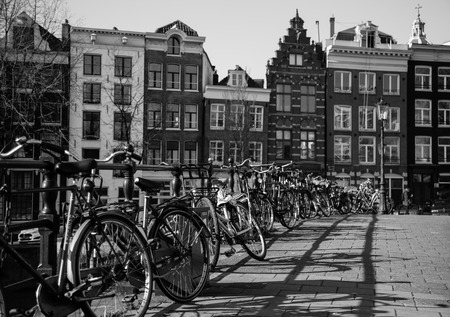 dutch canal house: AMSTERDAM, NETHERLANDS - 16TH FEBRUARY 2016: Lots of bikes chained to the railings of a bridge in Amsterdam. Typical Amsterdam style buildings can be seen in the background.