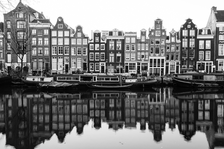 real renaissance: AMSTERDAM, NETHERLANDS - 16TH FEBRUARY 2016: A view of buildings and boats along the Amsterdam Canals. Reflections can be seen in the water. Editorial