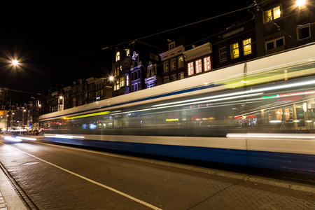 blurred motion: AMSTERDAM, NETHERLANDS - 16TH FEBRUARY 2016: A tram moving along a road in Amsterdam at night showing blurred motion. Editorial