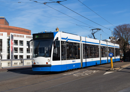 outside machines: AMSTERDAM, NETHERLANDS - 16TH FEBRUARY 2016: A typical blue and white Tram on a road in Amsterdam during the day. People can be seen on the tram.