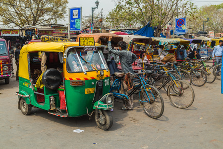 tuk tuk: DELHI, INDIA - 19TH MARCH 2016: Tuk Tuk Rickshaws parked on a street in central Delhi during the day. People can be seen.