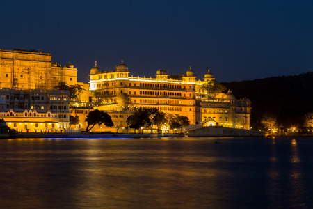 haveli: UDAIPUR, INDIA - 20TH MARCH 2016: A view towards the City Palace from Pichola Lake in Udaipur at night. Lights can be seen on the building. Editorial