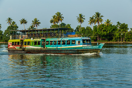 backwaters: KERALA BACKWATERS, INDIA - 1ST APRIL 2016: A colourful passenger boat in the Kerala backwaters of south India during the day. People can be seen.