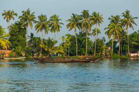 kerala culture: KERALA BACKWATERS, INDIA - 1ST APRIL 2016: A colourful passenger boat in the Kerala backwaters of south India during the day. People can be seen.