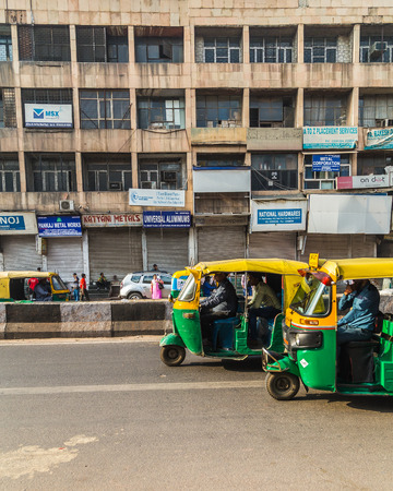 tuk tuk: DELHI, INDIA - 19TH MARCH 2016: Tuk Tuk Rickshaws on a street in central Delhi during the day. People and buildings can be seen. Editorial