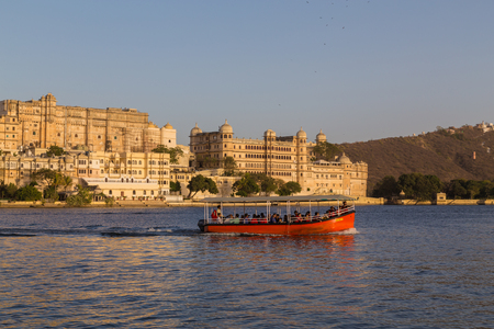 tour boats: UDAIPUR, INDIA - 20TH MARCH 2016: A view towards the City Palace from Pichola Lake in Udaipur during the day. Tour boats and people can be seen.