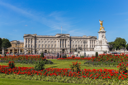 buckingham palace: LONDON, UK - 18TH JULY 2015: The outside of Buckingham Palace in London during the summer showing the Main Palace, Victoria Memorial and flowers. People can be seen outside.
