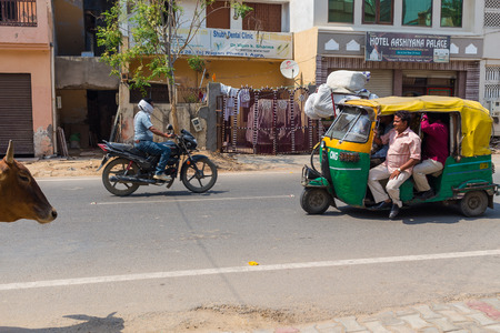 tuk tuk: AGRA, INDIA - 26TH MARCH 2016: Scenes along roads of Agra in India during the day. Tuk Tuk Rickshaws, Motorbikes, Cows, buildings and people can be seen.