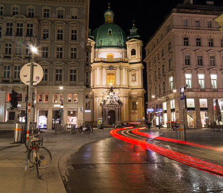 st  peter: VIENNA, AUSTRIA - 22ND APRIL 2016: The outside of the Catholic Church of St. Peter in Vienna at night from the Graben. Trails from traffic can be seen.
