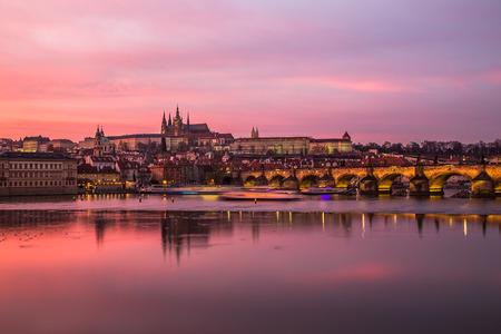 Karlsbrücke in Prag, in Richtung der Kleinseite und der Prager Burg bei Sonnenuntergang mit einem bunten vibrierenden rosa Himmel.