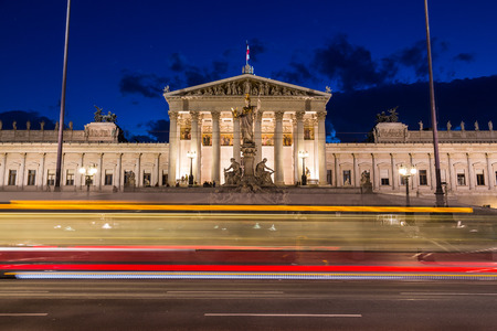 innere: The outside of the Austrian Parliament building in Viennat at night. The blur of a tram can be seen going past in the foreground.