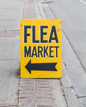 common market: Sign and Arrow for a Flea Market on a street