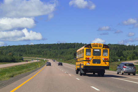 scotia: NOVA SCOTIA, CANADA - 28TH AUGUST 2014: School Bus and rural roads in Nova Scotia Canada during the day.