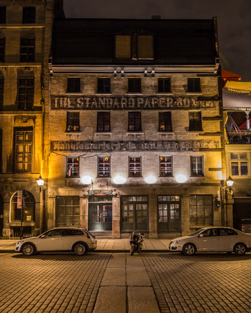 est: MONTREAL, CANADA - 17TH MAY 2015: A view of buildings along Rue de la Commune in Old Montreal at night.