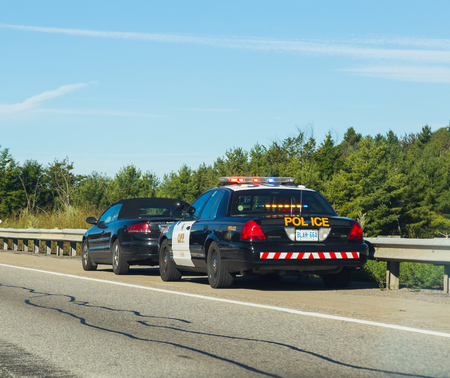 pulled over: CANADA - 29TH AUGUST 2014: A car that has been pulled over by the police on a road in Canada.