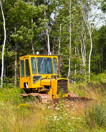 outside machines: NOVA SCOTIA, CANADA - 27TH AUGUST 2014: A small bright yellow tractor parked in a field.