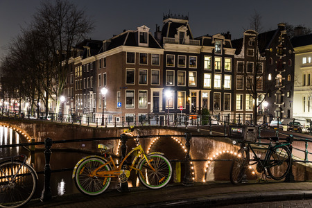 dutch canal house: AMSTERDAM, NETHERLANDS - 17TH FEBRUARY 2016: Bridges, buildings and bikes at the Leidsegracht and Keizersgracht canal intersection in Amsterdam at night.