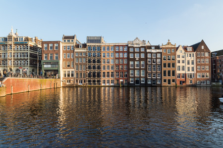 dutch canal house: AMSTERDAM, NETHERLANDS - 17TH FEBRUARY 2016: Old Buildings along the Damrak in Amsterdam during the day. People can be seen.