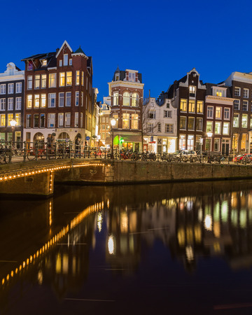 decorated bike: AMSTERDAM, NETHERLANDS - 16TH FEBRUARY 2016: A view along the Keizersgracht canal in Amsterdam at night. Buildings, bridges, cars and bikes can be seen.