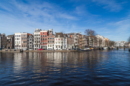 dutch canal house: AMSTERDAM, NETHERLANDS - 16TH FEBRUARY 2016: A view along canals in Amsterdam during the day. Buildings, boats and people can be seen.