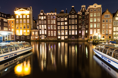 dutch canal house: AMSTERDAM, NETHERLANDS - 16TH FEBRUARY 2016: Old Buildings along the Damrak in Amsterdam at night. Boats and reflections can be seen.