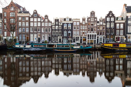 real renaissance: AMSTERDAM, NETHERLANDS - 16TH FEBRUARY 2016: A view of buildings along the Amsterdam Canals. Reflections can be seen in the water.