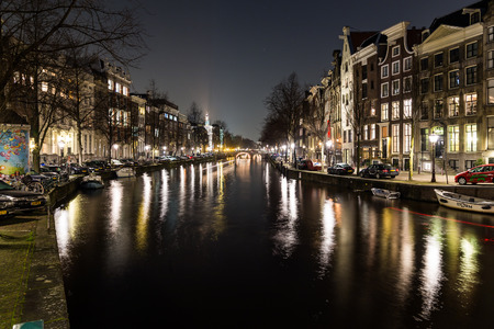 dutch canal house: AMSTERDAM, NETHERLANDS - 17TH FEBRUARY 2016: Buildings and bikes at the Keizersgracht canal intersection in Amsterdam at night. Editorial