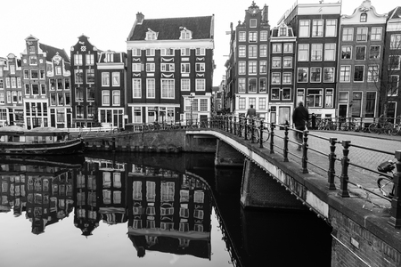 real renaissance: AMSTERDAM, NETHERLANDS - 16TH FEBRUARY 2016: A view of buildings and bridges along the Amsterdam Canals. People can be seen. Editorial